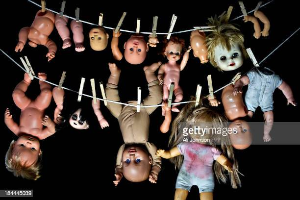 CONTENT] Plastic dolls some in pieces hang from a clothesline