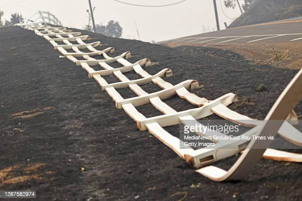Plastic fence lays on the charred grass after being destroyed by the fire on Pleasants Valley Road in Vacaville, Calif., on Thursday, Aug. 20, 2020....
