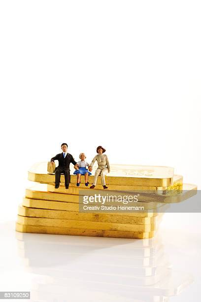 Figurines of family sitting on gold bars against white background