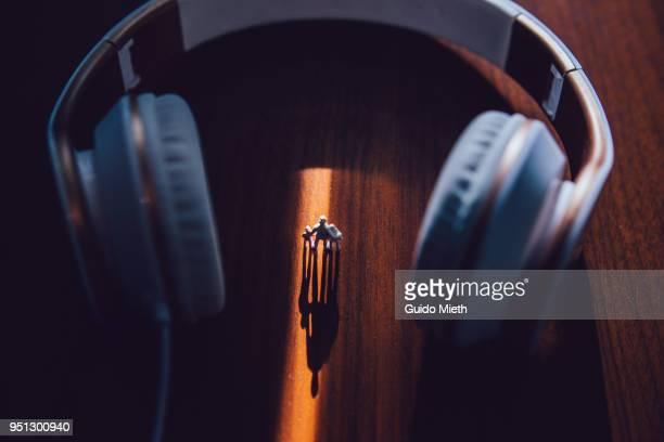Plastic figurines standing between big earphones
