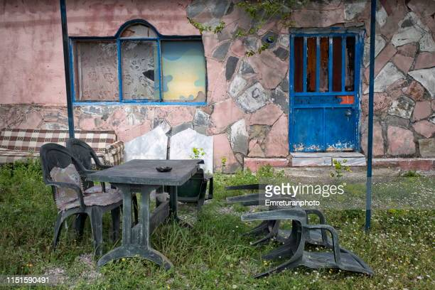 plastic furniture in front of an abandoned house. - emreturanphoto stock pictures, royalty-free photos & images
