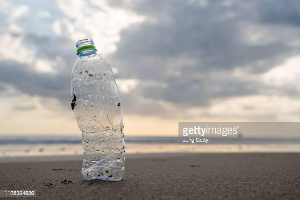 plastic garback  on sand beach - pollution de l'eau photos et images de collection