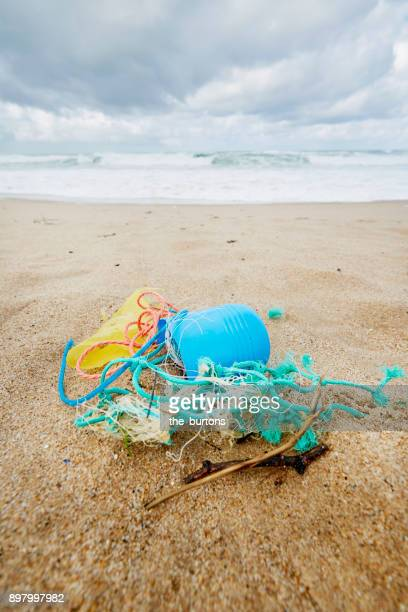 plastic garbage on the beach - plastic pollution stock pictures, royalty-free photos & images