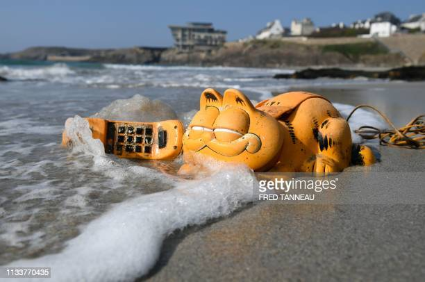 A plastic 'Garfield' phone is displayed on the beach on March 30 2019 in Le Conquet western France For more than 30 years plastic phones in the shape...