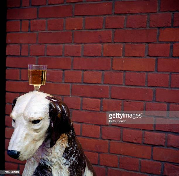 A plastic glass of champagne on the head of a dogshaped charity donation box at Royal Ascot Racecourse June 2002