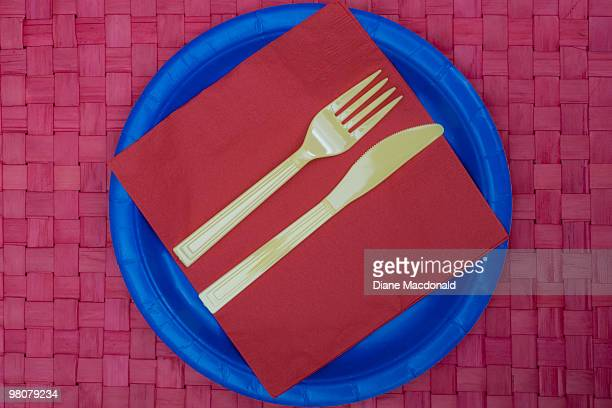 plastic knife and fork and napkin on a paper plate - paper plate stock photos and pictures