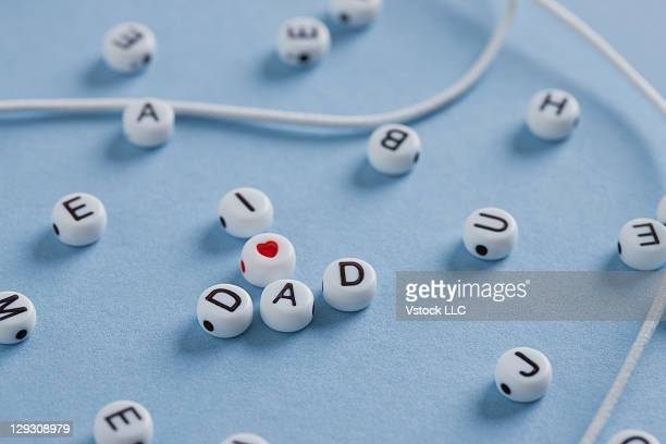 PLastic letters forming word dad on blue background