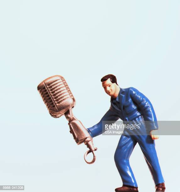 plastic man holding microphone - big mike stock pictures, royalty-free photos & images