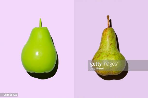 plastic pear beside real pear - pear stock pictures, royalty-free photos & images