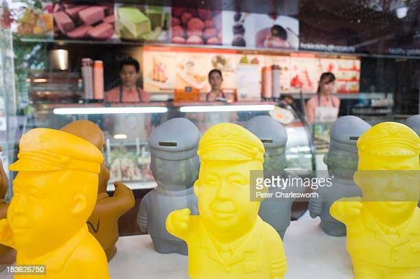 Plastic 'piggy banks' in the form of Tan Passakornnatee - Founder and CEO of Ichitan, a Thai tea drinks and restaurant company - line the window of...