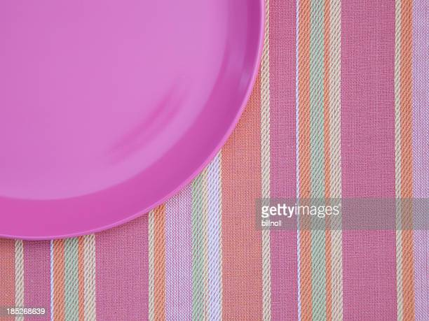plastic plate on pastel colored placemat - plastic plate stock pictures, royalty-free photos & images