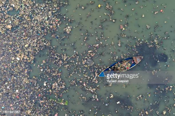 plastic pollution in the ocean; man cleaning plastic pollution in the sea - プラスチック汚染 ストックフォトと画像