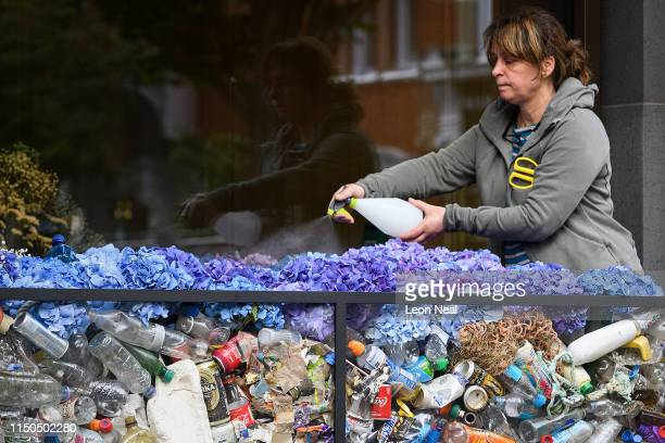 Plastic refuse collected from beaches by Surfers Against Sewage is seen beneath the floral arrangement in a window display of Marshall Wace global...