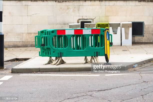plastic road construction barriers on a city sidewalk - construction barrier stock pictures, royalty-free photos & images