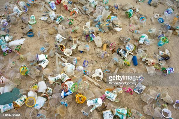 plastic rubbish on selong belanak beach - plastic pollution stock pictures, royalty-free photos & images