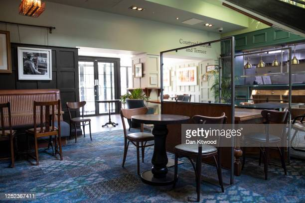Plastic screens are installed between tables at a branch of Weatherspoons in Muswell Hill as it prepares for reopening on June 25 2020 in London...