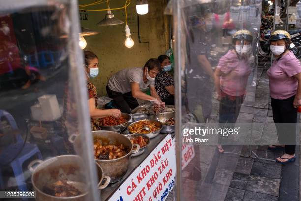 Plastic sheet dividers are set up at stores at a wet market to minimize physical interaction between store owners and shoppers on September 21, 2021...