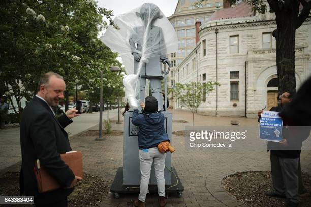 A plastic sheet keeps the rain off a mock statue of Attorney General Jeff Sessions before protesters topple it in front of the Department of Justice...