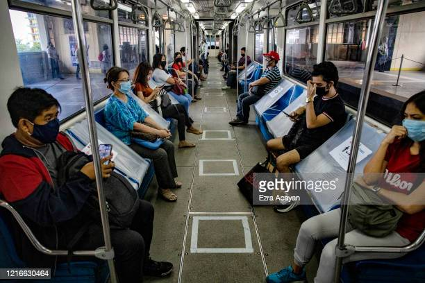 Plastic sheets separate commuters seated inside a train as part of social distancing measures, on the first day of relaxed quarantine measures on...