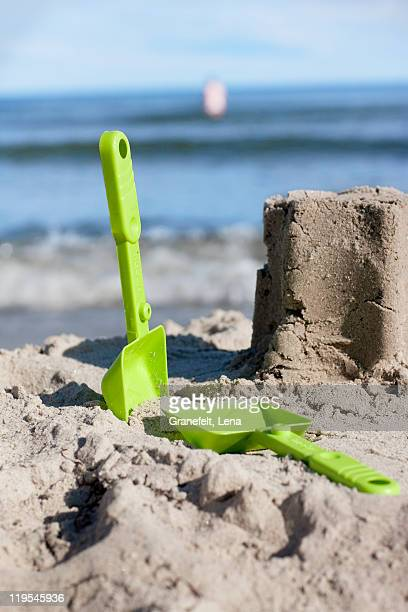 Plastic shovels and sand castle on beach