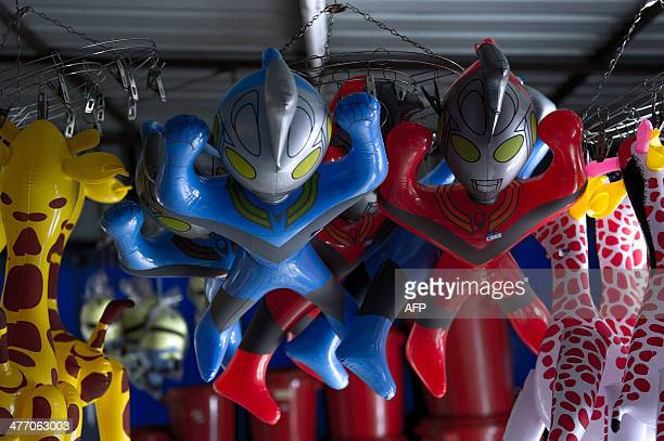 Plastic toys of Japanese animation superhero 'Ultraman' hang from the ceiling of a shop for sale in Karak some 80 kilometres east of Kuala Lumpur on...