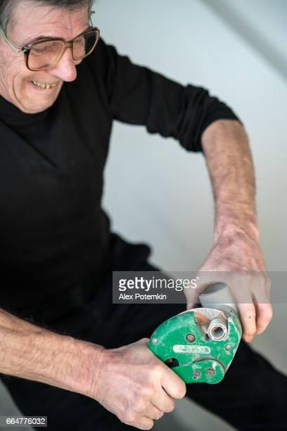 Plastic buizen snijden. 70-jaar-oud actieve senior man, bouwvakker - loodgieter, die werkt voor home renovatie