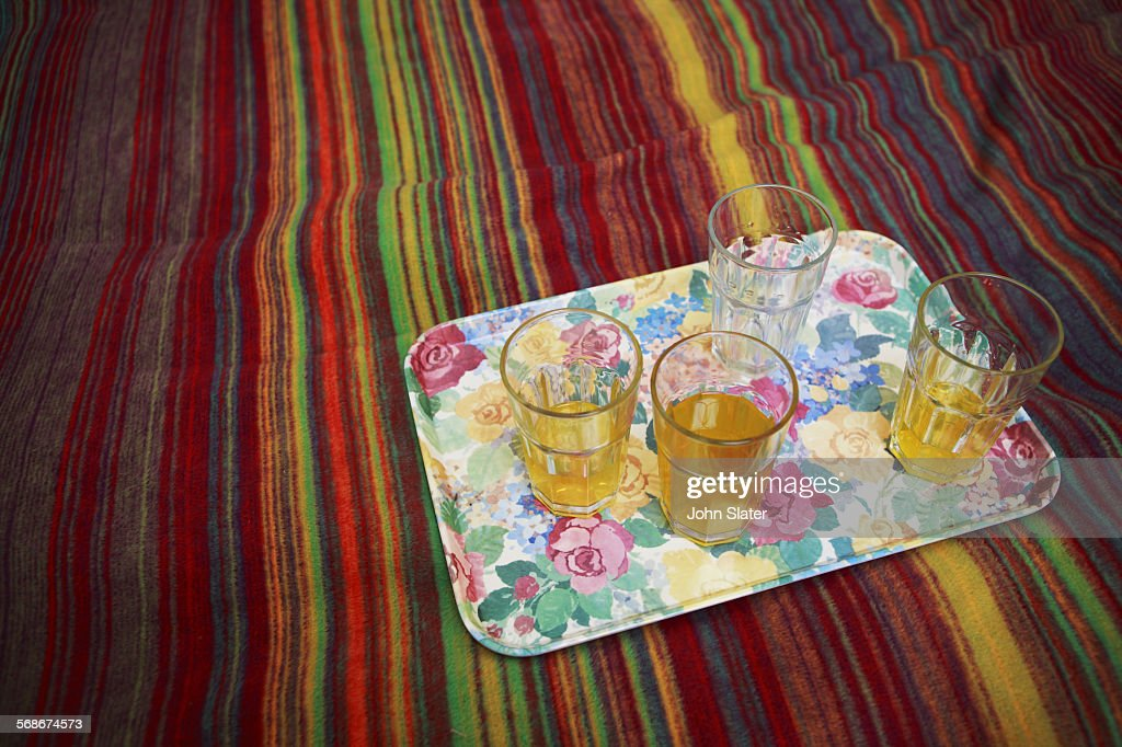 Plastic tumblers of juice on a tray and bed : Stock Photo