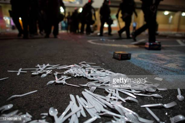 Plastic utensils scatter across a parking lot as police investigate a looted grocery store during widespread unrest following the death of George...