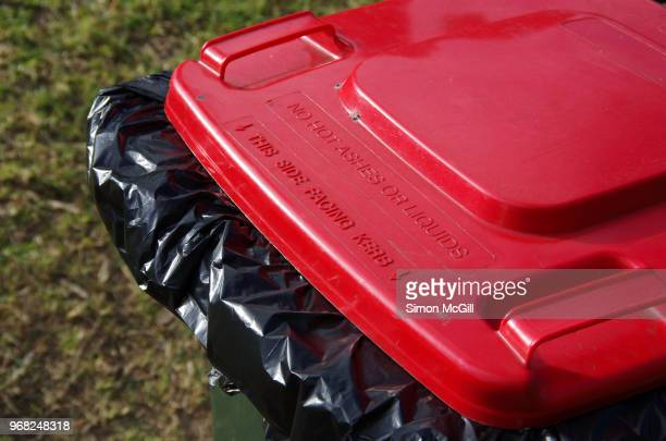 Plastic wheelie garbage bin with a red lid on the grass verge of a suburban street