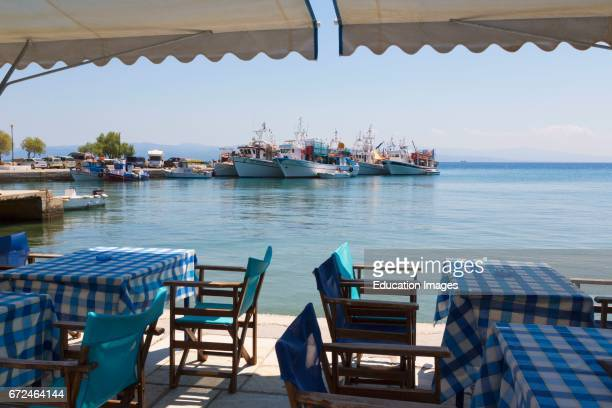 Platanias Thessaly Greece Tables and chairs outside a harbor side restaurant Fishing boats in the distance