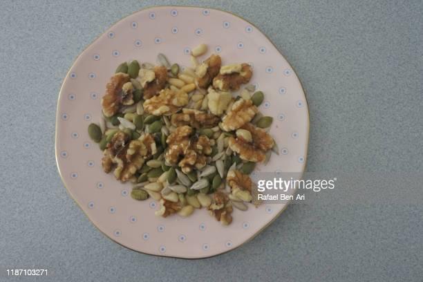 plate full of edible seeds and nuts flat lay - rafael ben ari stock-fotos und bilder