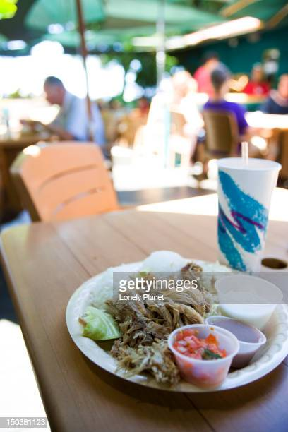 plate lunch at aloha mixed plate cafe. includes kahlua pork, centre, lomi lomi salmon, right foreground cup, poi, centre right cup, haupia, rear right cup.  also macaroni salad and rice. - poi_(food) stock pictures, royalty-free photos & images