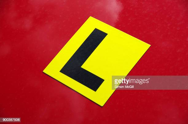 L plate magnetic label on a red car hood