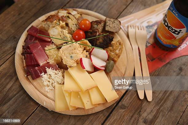 A plate of alm cheese alpine bacon obazda cheese pretzel casserole with brie onion confit a minced meat patty apple horse radish and a pickel await a...