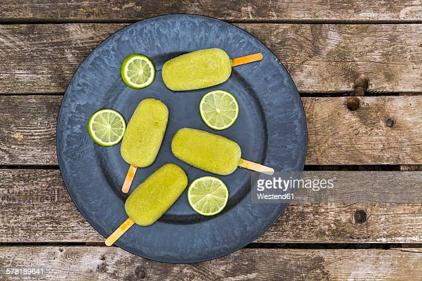 Plate of avocado ice lollies and slices of lime
