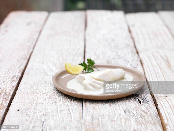 Plate of bake in bag haddock mornay on wooden table