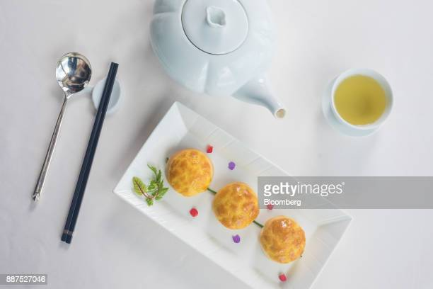 A plate of baked barbecued pork buns with pine nuts is arranged for a photograph at Lung King Heen restaurant at the Four Seasons Hotel in Hong Kong...