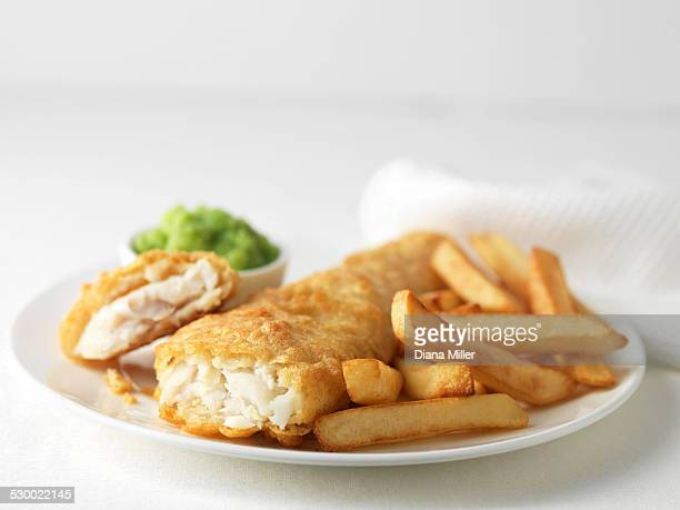 Plate of battered cod and chips with mushy peas