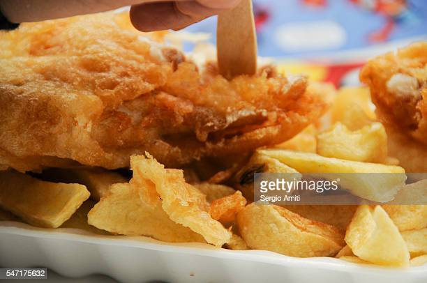 A plate of battered fish and chips with a wooden disposable fork