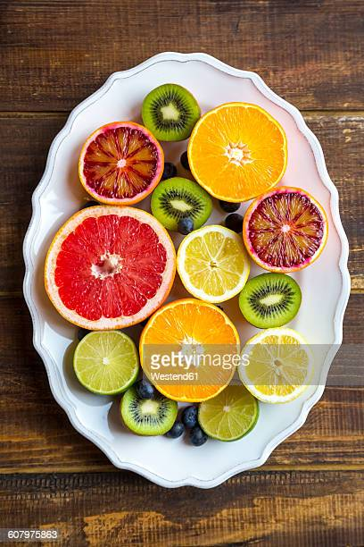 Plate of blueberries, kiwis and sliced citrus fruits on wood