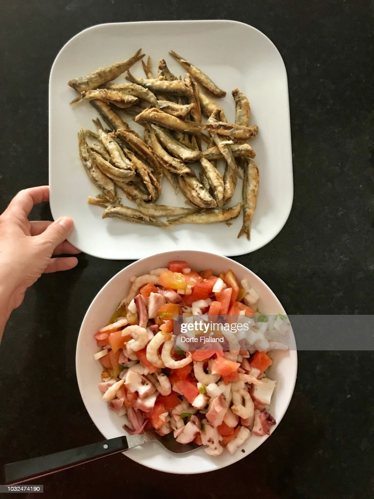 Plate of boquerones (small sardines) and a seafood, tomato salad on a black counter : Foto de stock