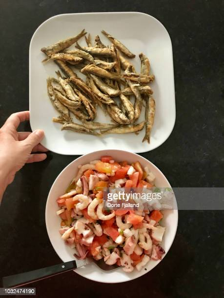 Plate of boquerones (small sardines) and a seafood, tomato salad on a black counter