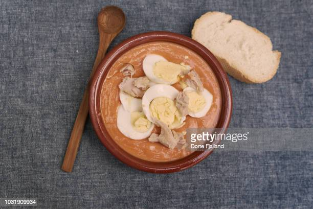 Plate of brown clay with salmorejo, a wooden spoon and a slice of bread on blue table cloth