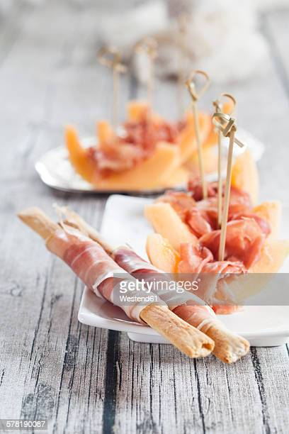 Plate of Charentais melon slices with ham and Grissini wrapped with ham