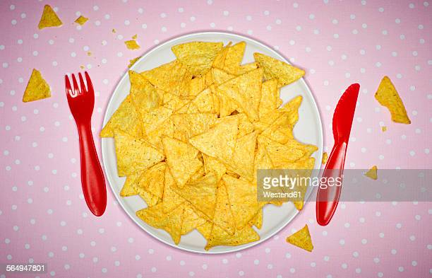 Plate of cheese nachos and red plastic cutlery on pink cloth