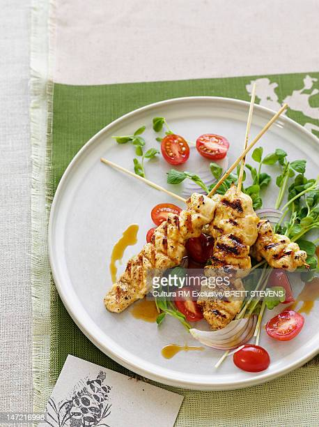Plate of chicken skewers and salad
