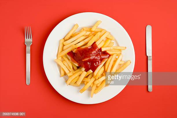 Plate of chips and tomato sauce, overhead view