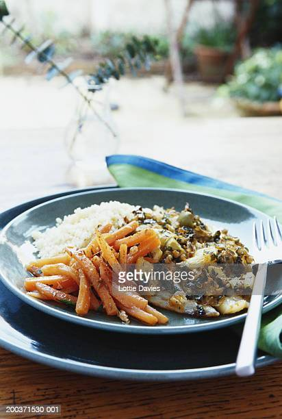 Plate of cod and chermoula on outdoor table, close-up