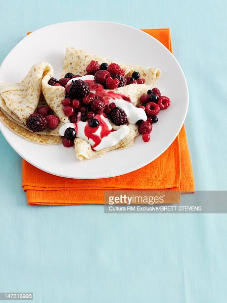 Plate of crepes with berries and cream