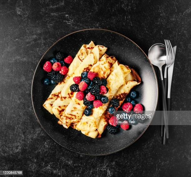 plate of crepes with berries on black background - pancakes stock pictures, royalty-free photos & images